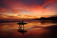 silhouette of man carrying surfboard during sunset