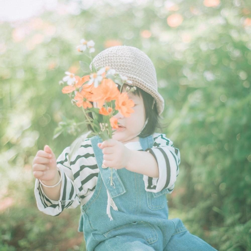 girl wearing hat holding orange flower
