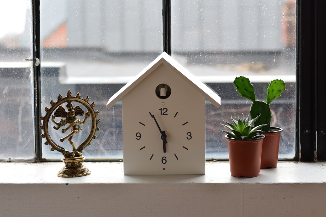 white wooden house analog clock reading 5:55