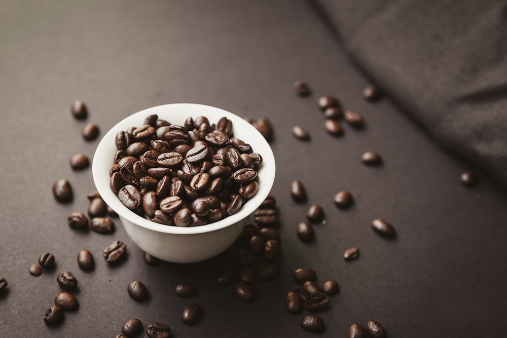 roasted coffee beans spilling out of white ceramic cup