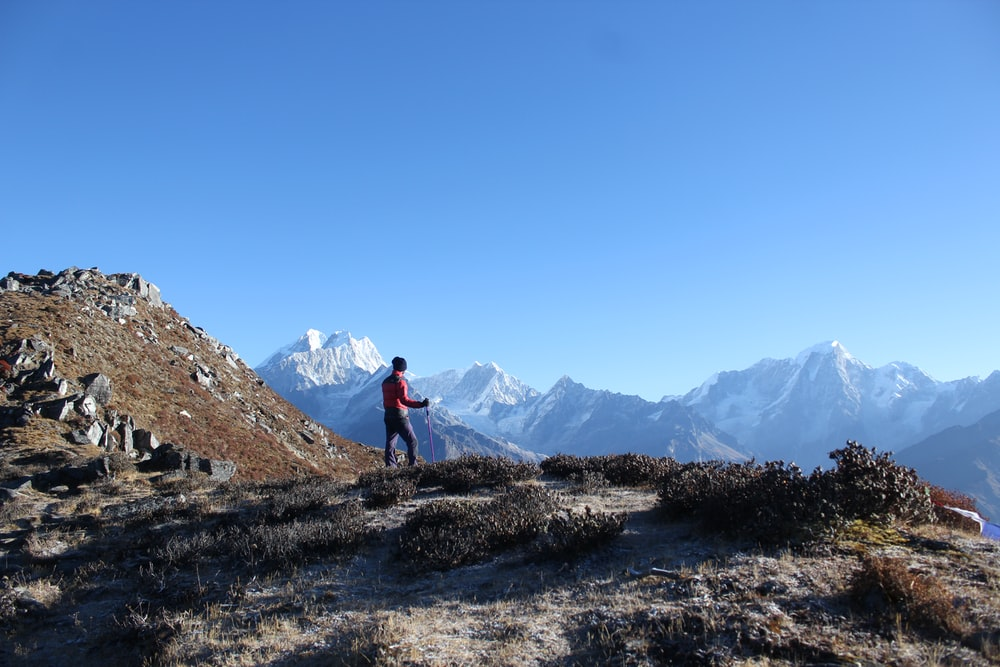 person standing on mountain under blue sky