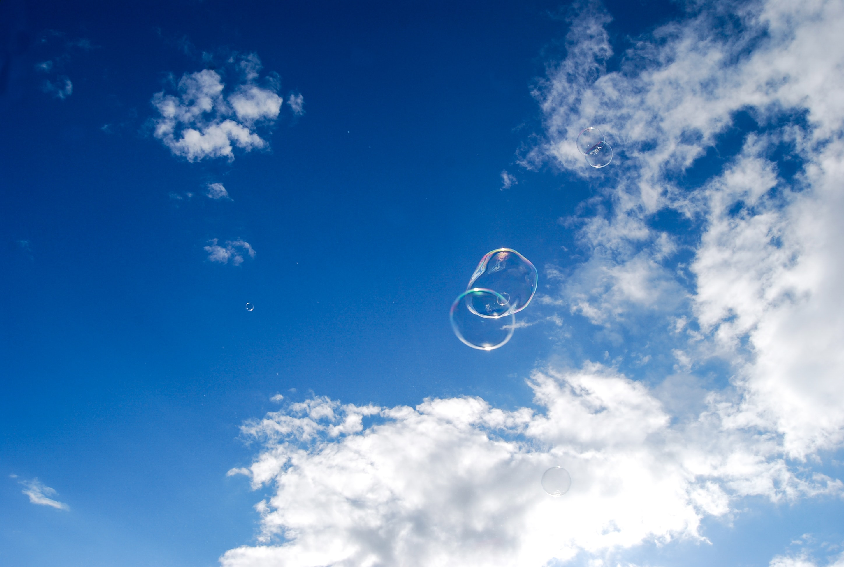 two bubbles under blue sky and white clouds during daytime