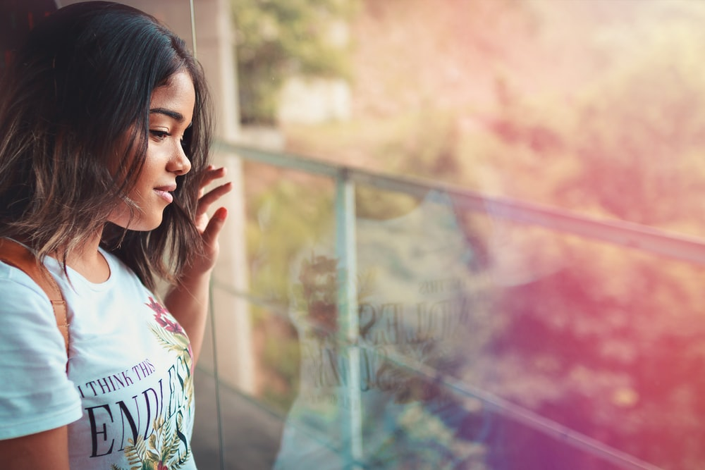 woman in white top leaning by glass wall during daytime