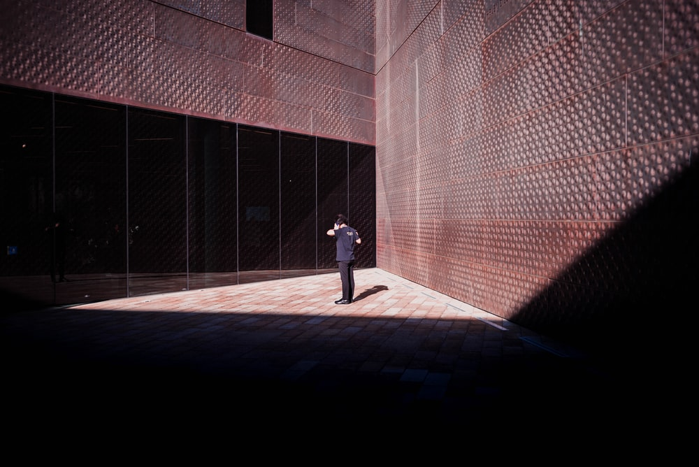 person standing between brown wall