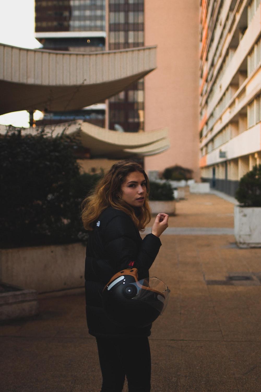 woman wearing black jacket outside building