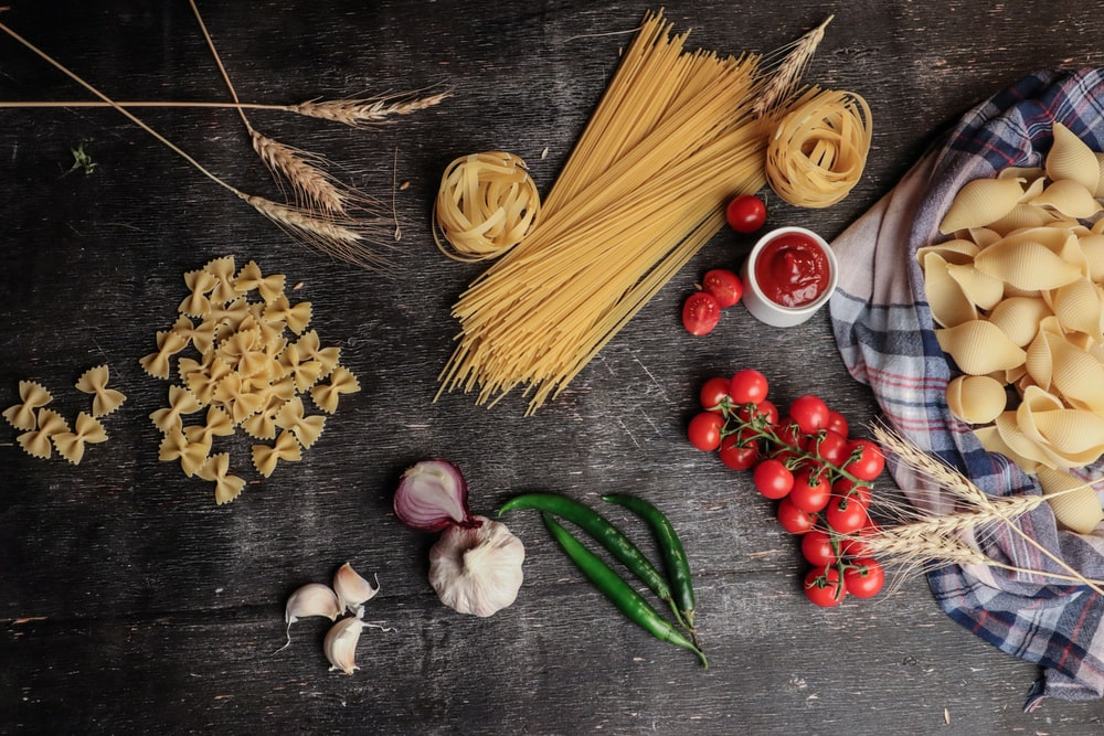 flatlay photo of pasta noodles, tomatoes, tomato sauce, onions, and garlic