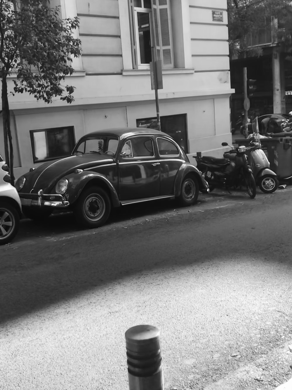 grayscale photo of black Volkswagen Beetle parked at roadside