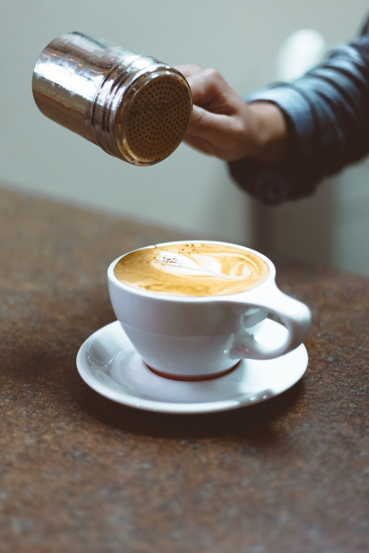 person pouring foam on cappuccino coffee