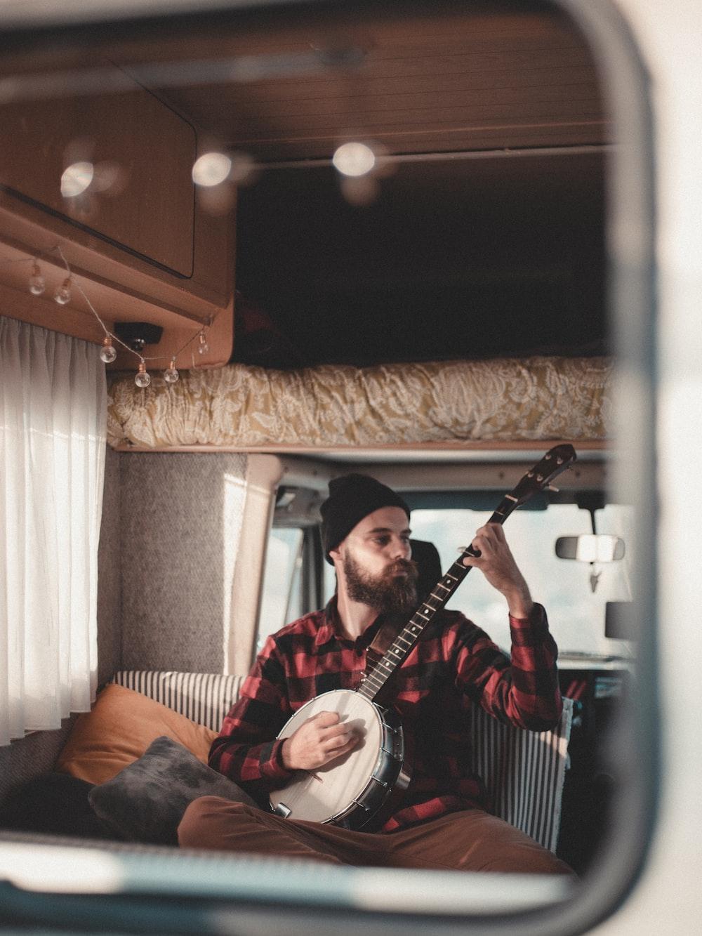 man sitting inside vehicle while playing mandoline