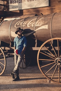man in blue chambray sports shirt leaning on Coca-Cola barrel