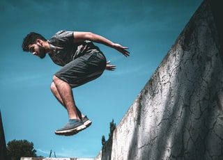 man jumping over wall during daytime