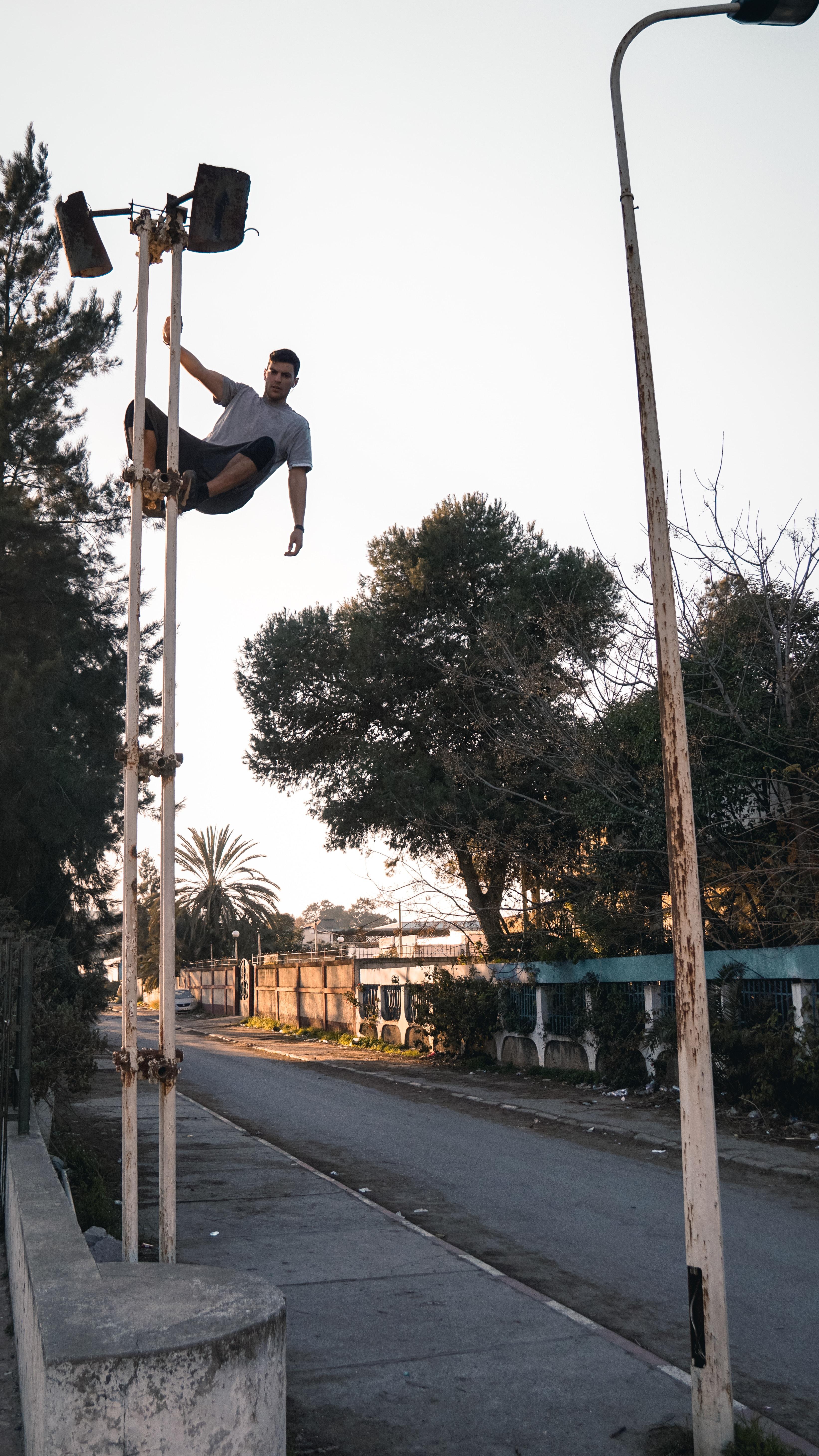 man climbing on outdoor light during daytime