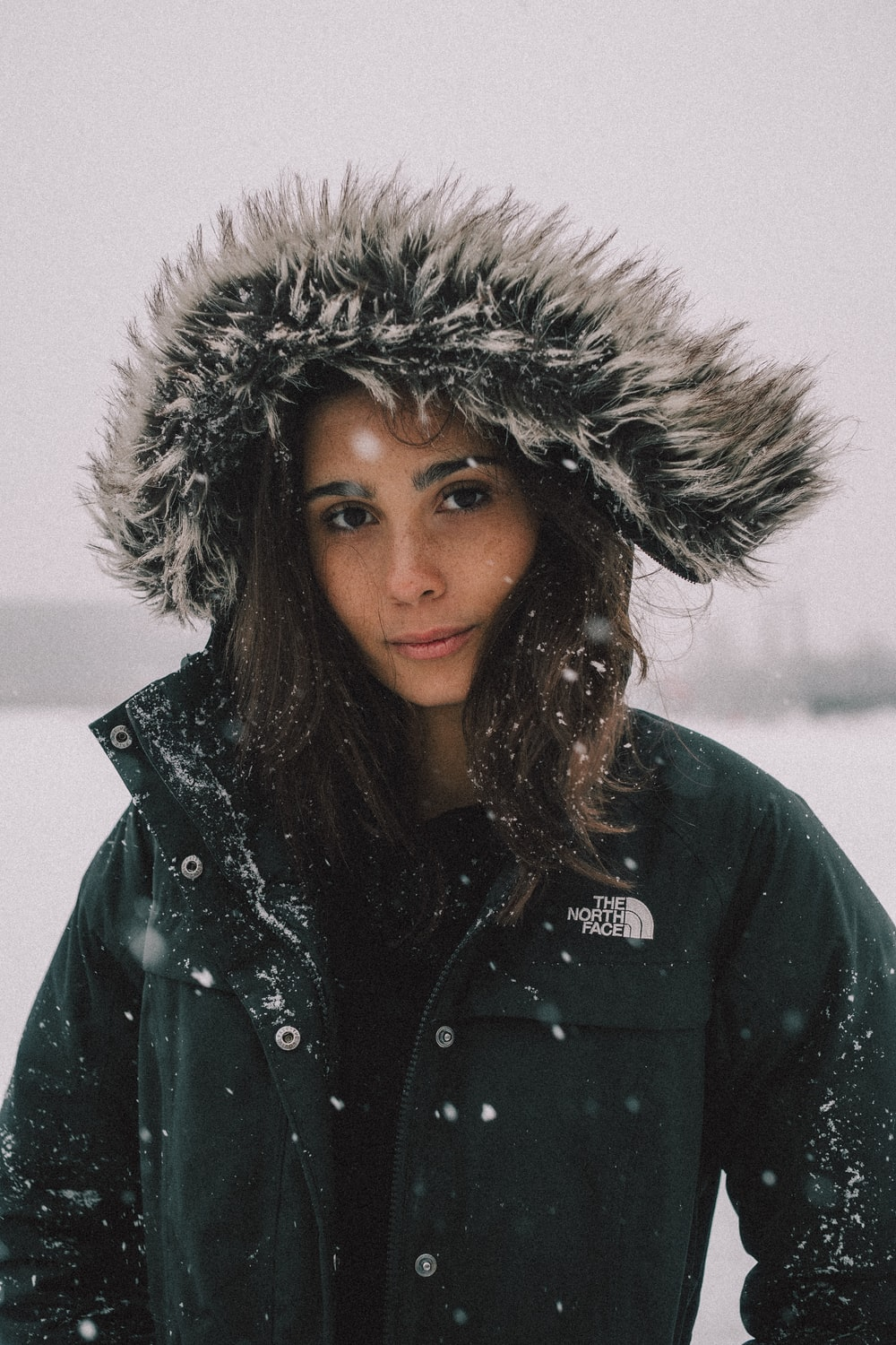 woman in black and white The North Face faux fur coat under snow