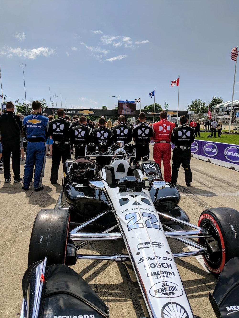 men standing behind racing cart