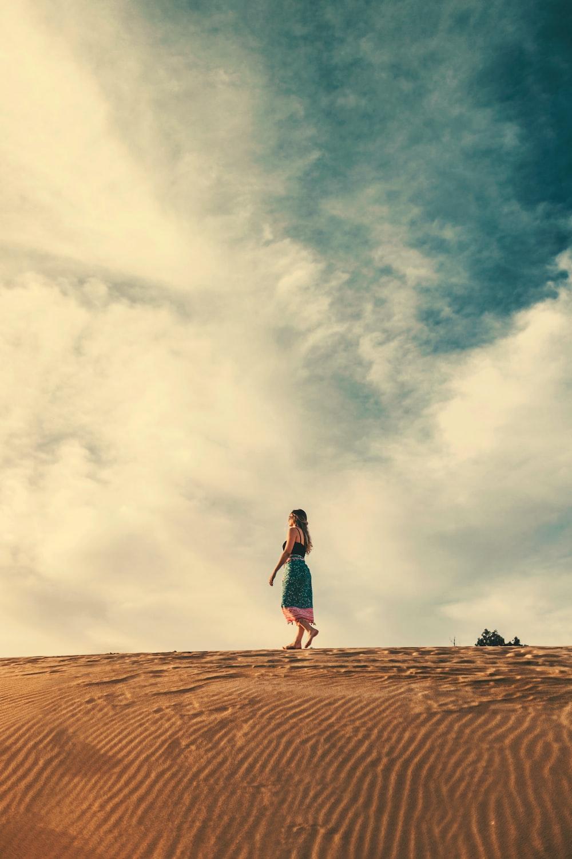 woman in skirt walks on sand barefoot