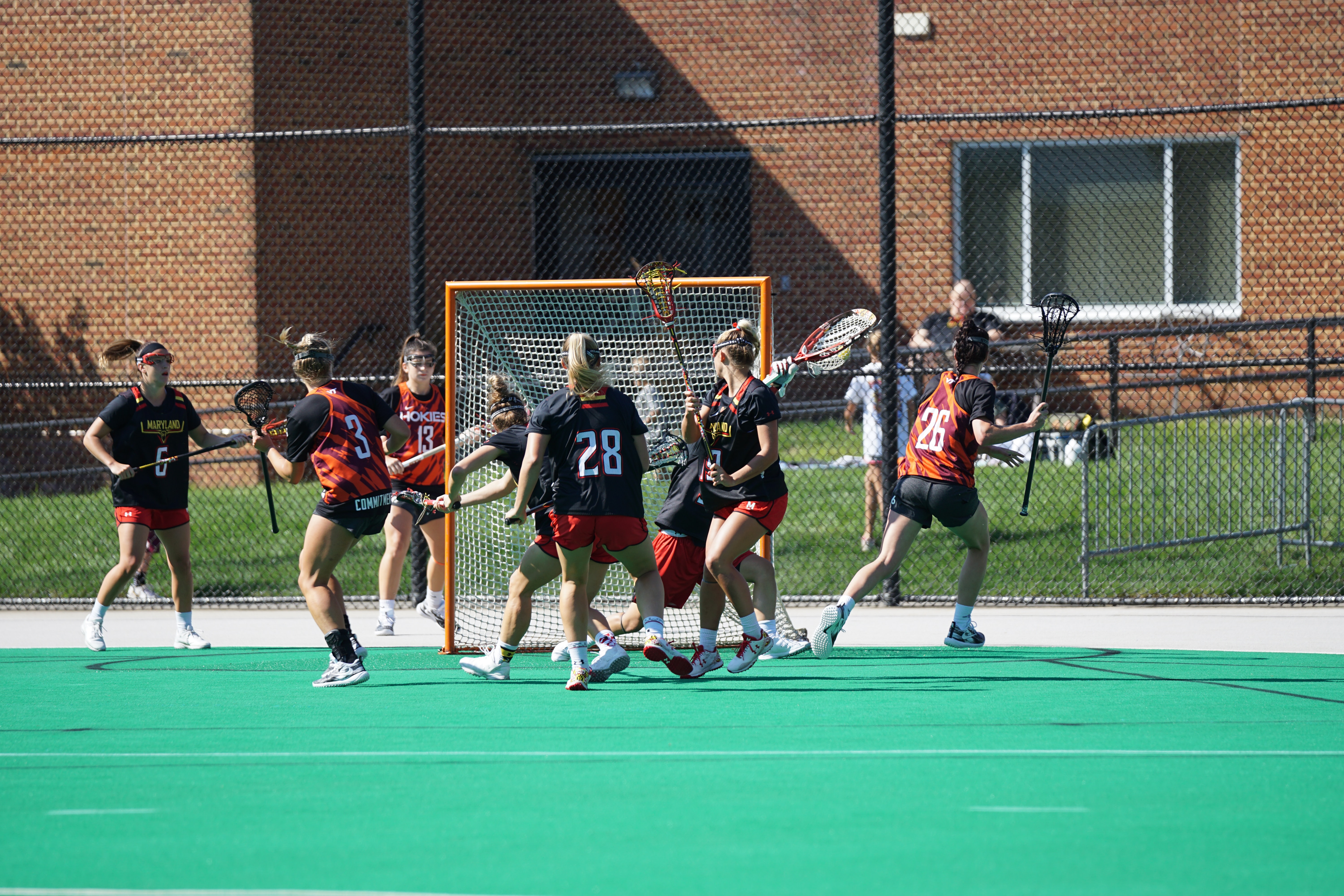 group of woman playing lacrosse during daytime