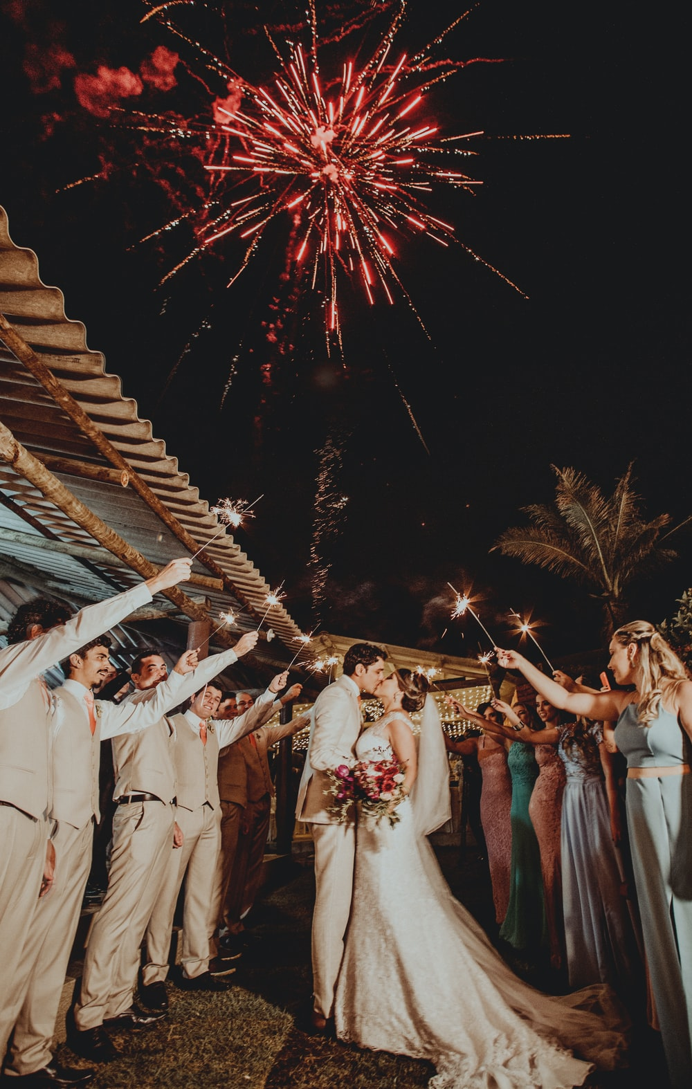 man and woman wedding couple kissing under fireworks