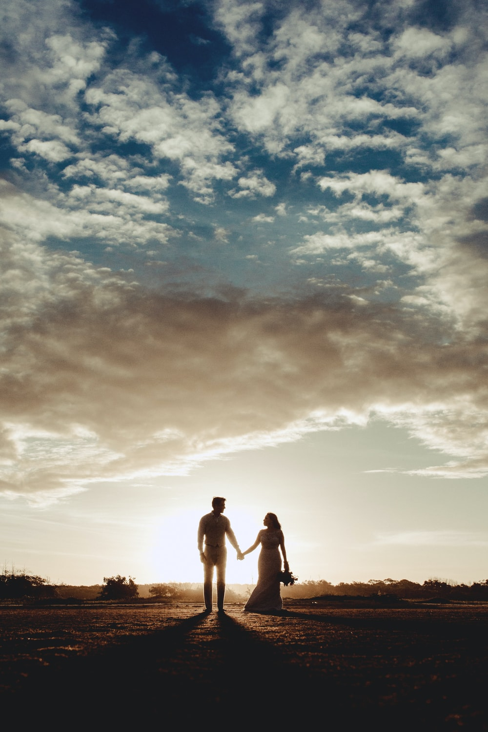 silhouette photo of man and woman under clear blue sky