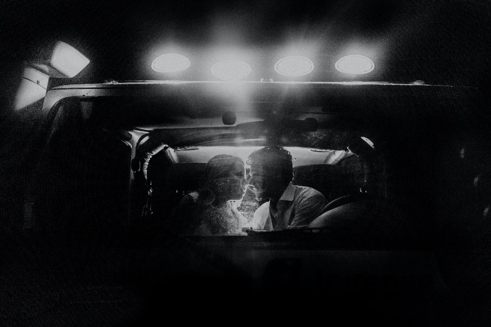 lighted kissing couple inside car