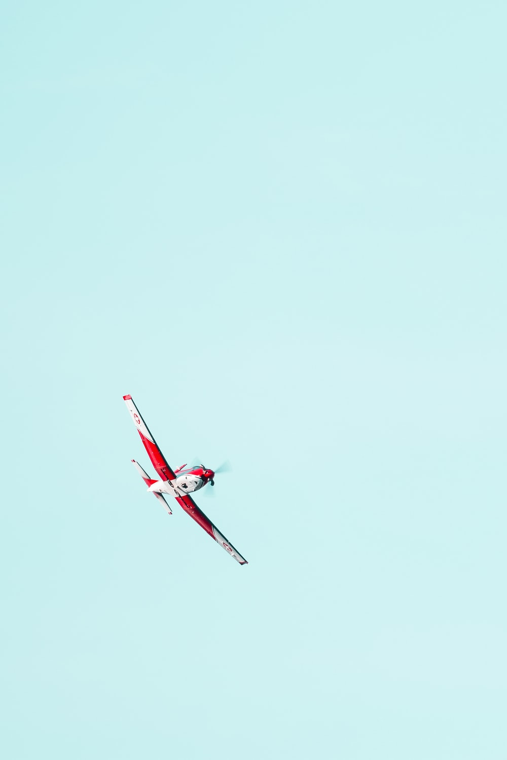 flying red and white biplane