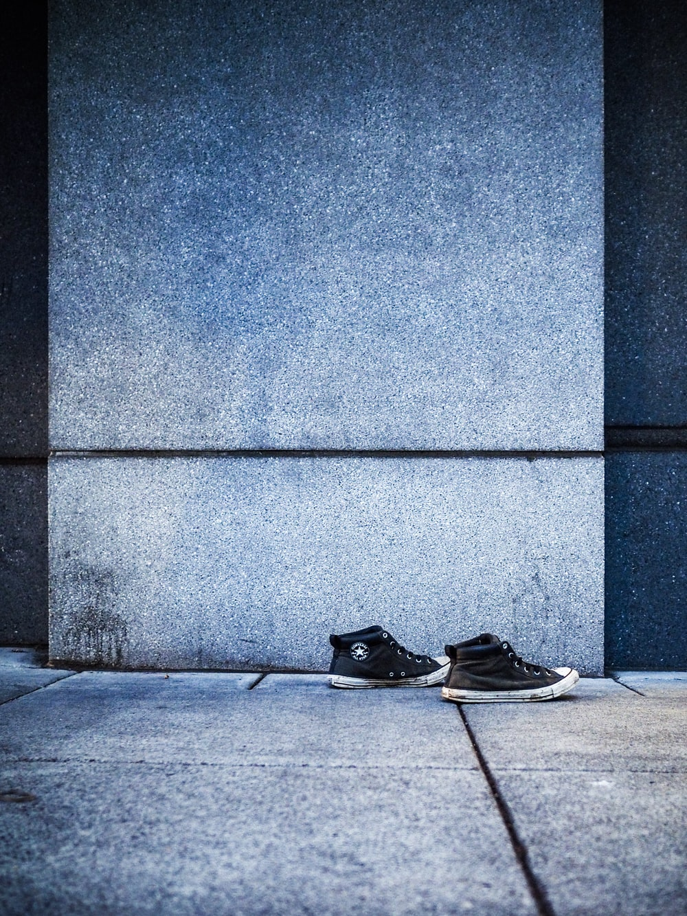 black-and-white high-top sneakers beside gray wall
