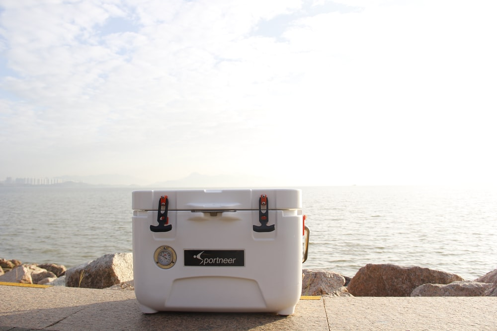 white cooler box on brown concrete pavement near body of water