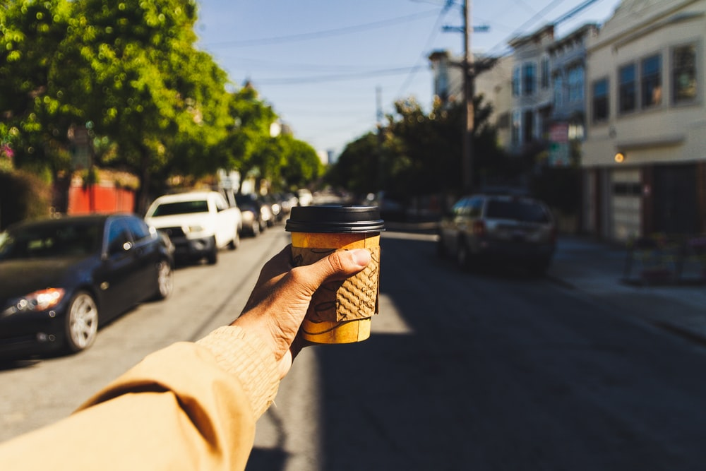 person holding brown and black disposable cup on road