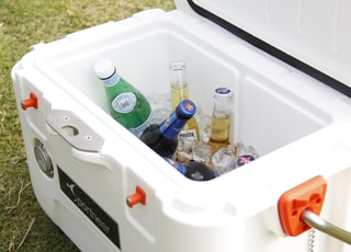 white ice cooler with assorted-brand bottle lot