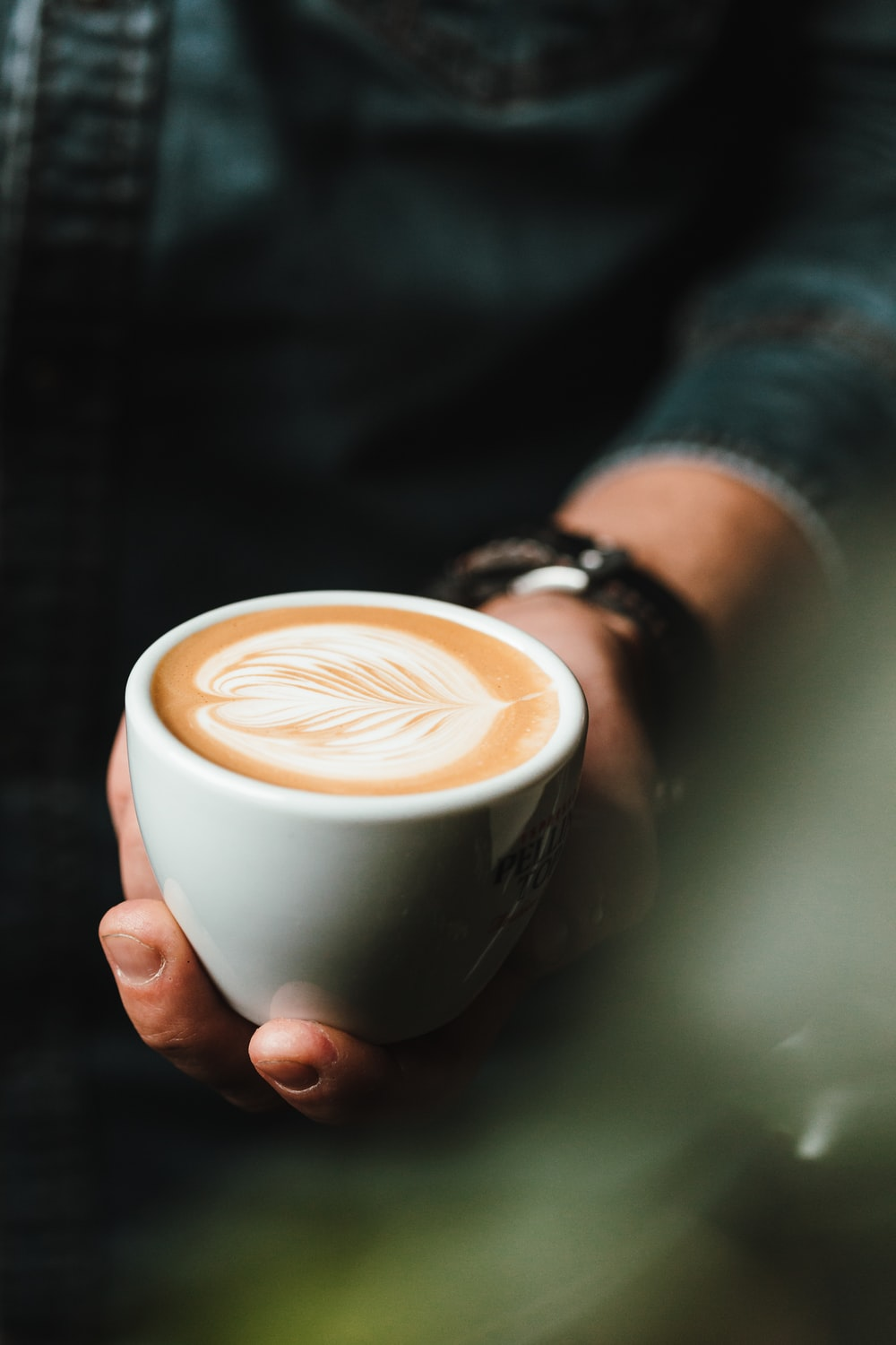 person holding cup of cappuccino