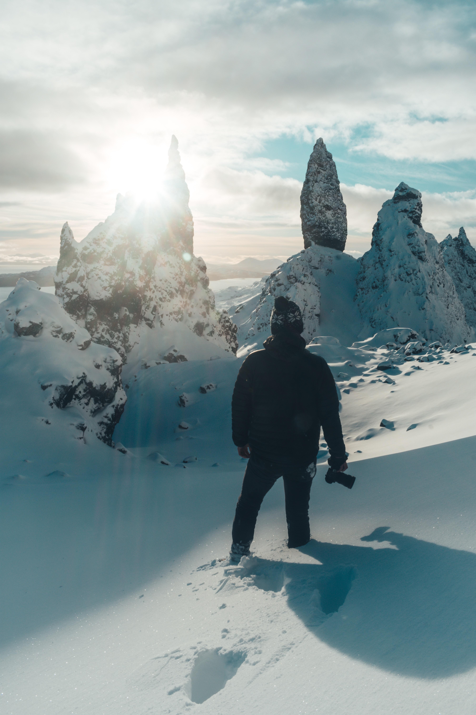man standing on snow ground while wearing black jacket
