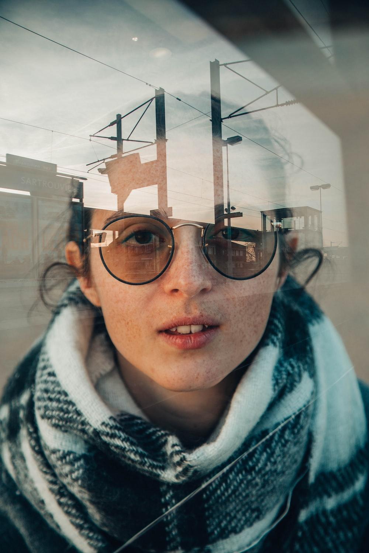 woman wearing sunglasses inside glass panele