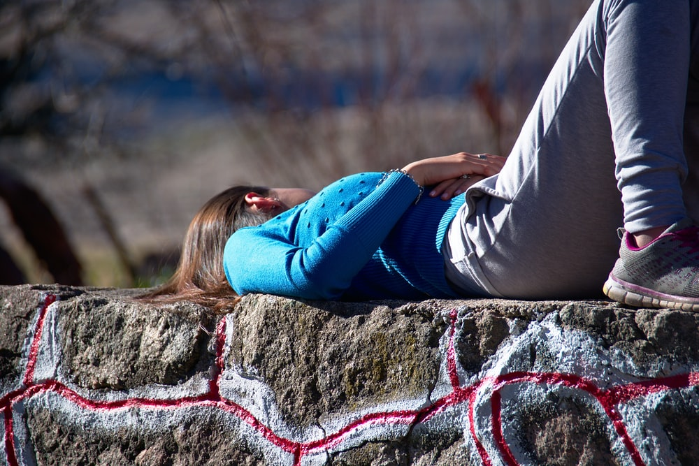 woman in blue long-sleeved top and gray sweatpants lying on concrete surface