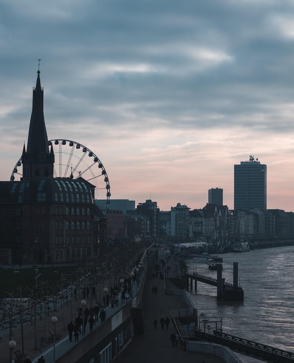 people walking on bridge near Ferris Wheel during daytime