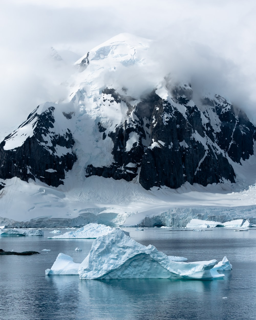 small iceberg beside large iceberg