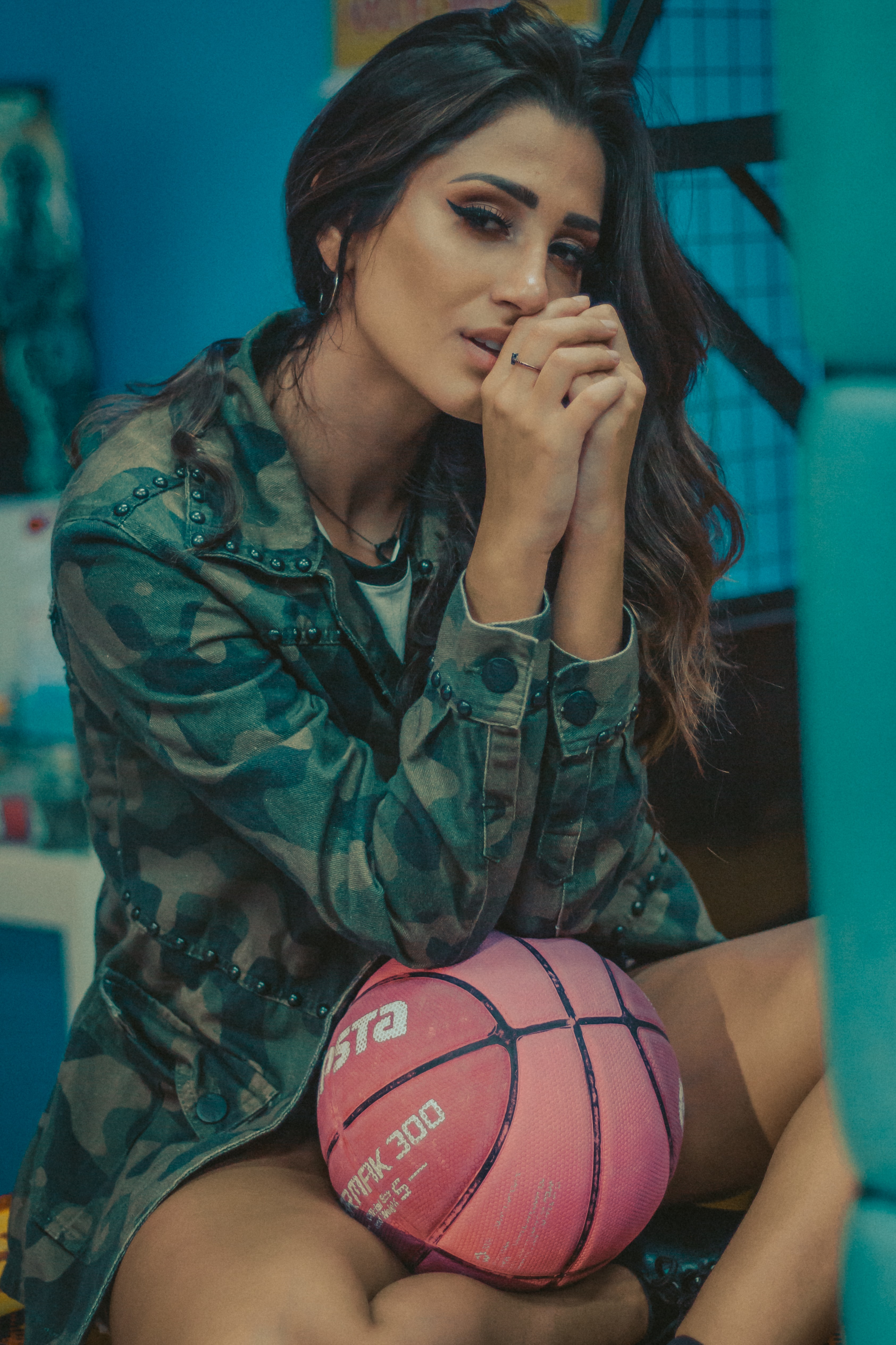 woman wearing camouflage jacket leaning her elbow on basketball on lap