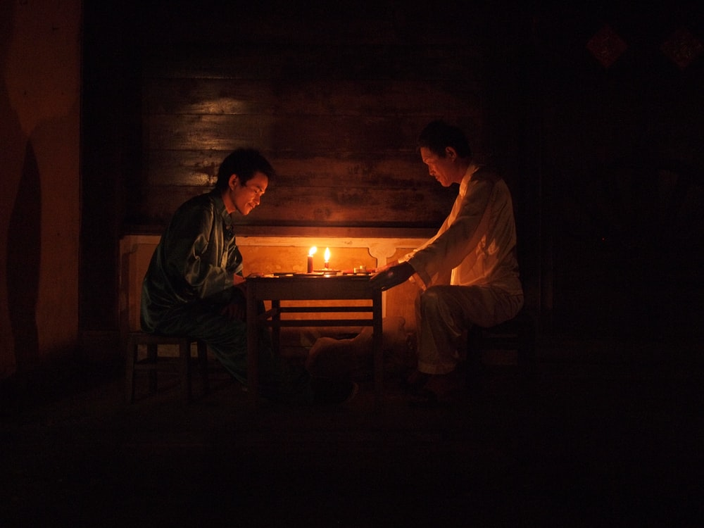 two men sitting by the table with candle lighted on
