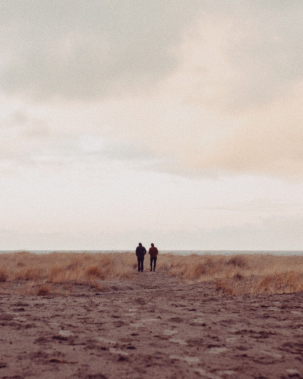 two people standing on sand