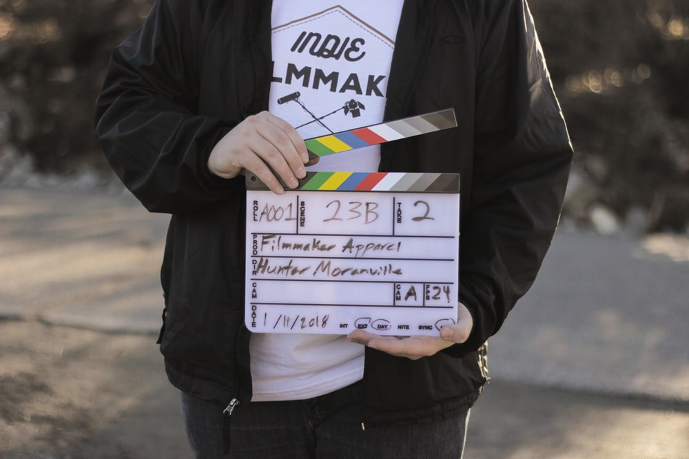 person in black jacket holding white director's cut