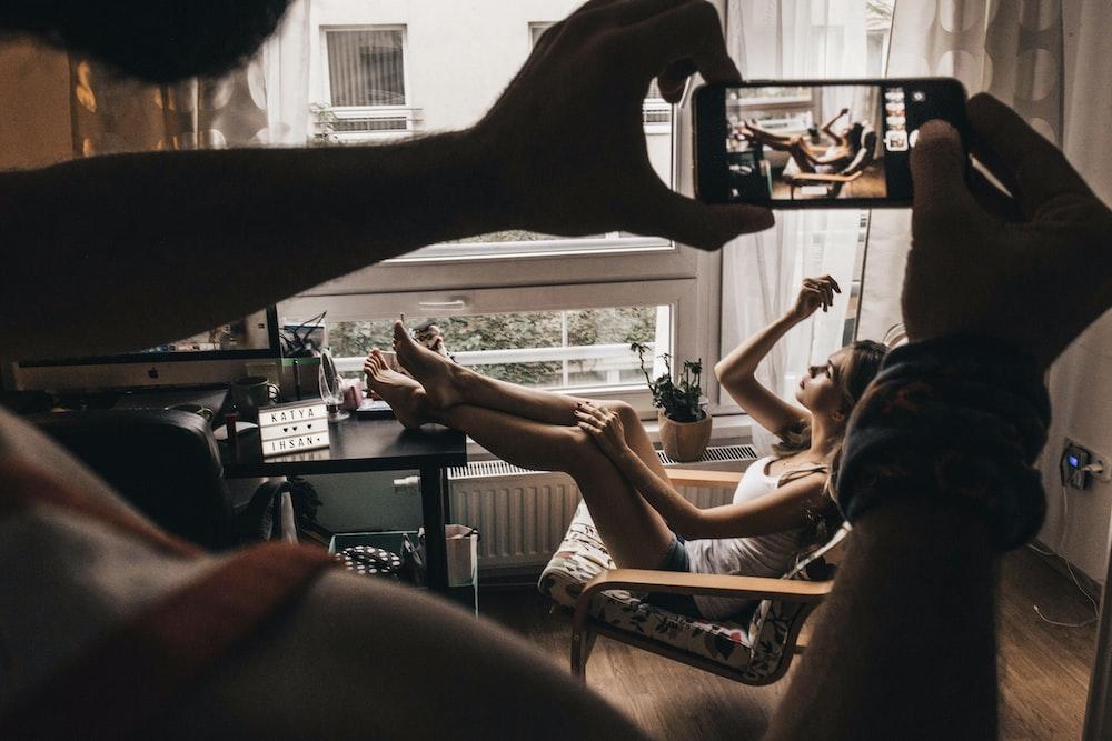 man taking photo of woman sits on chair near window using smartphone