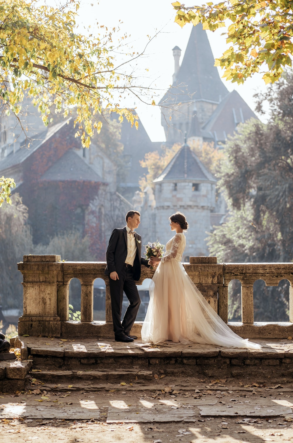 woman in white wedding dress stands in front of man in tuxedo
