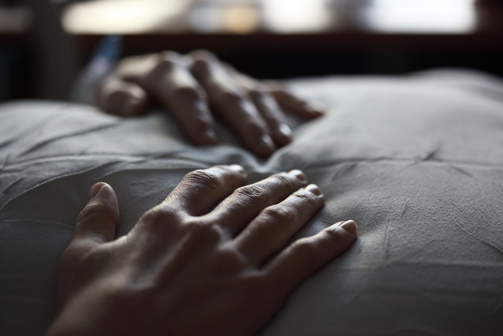 person's hand on white textile