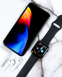 black aluminum case Apple Watch with black Sport Band and Apple AirPods on white surface