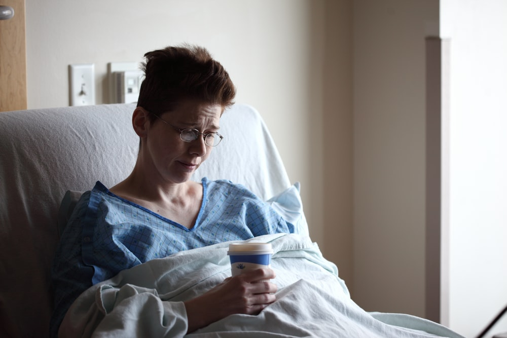woman on bed holding plastic cup