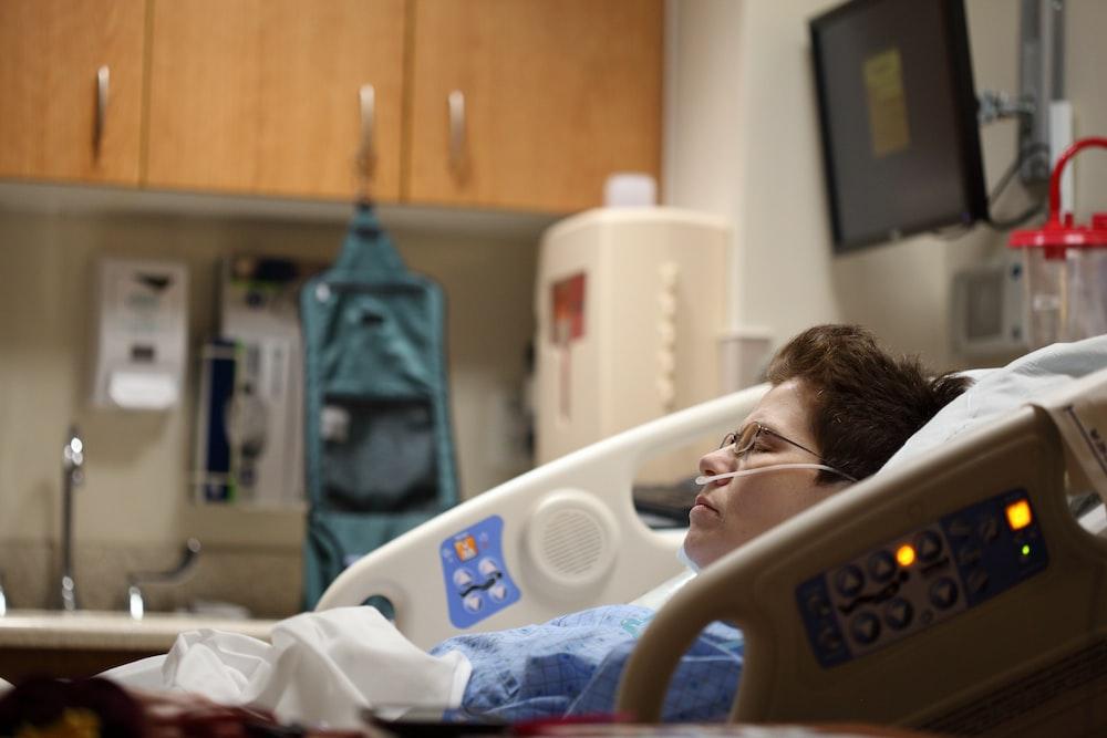 boy lying on beige recliner hospital bed