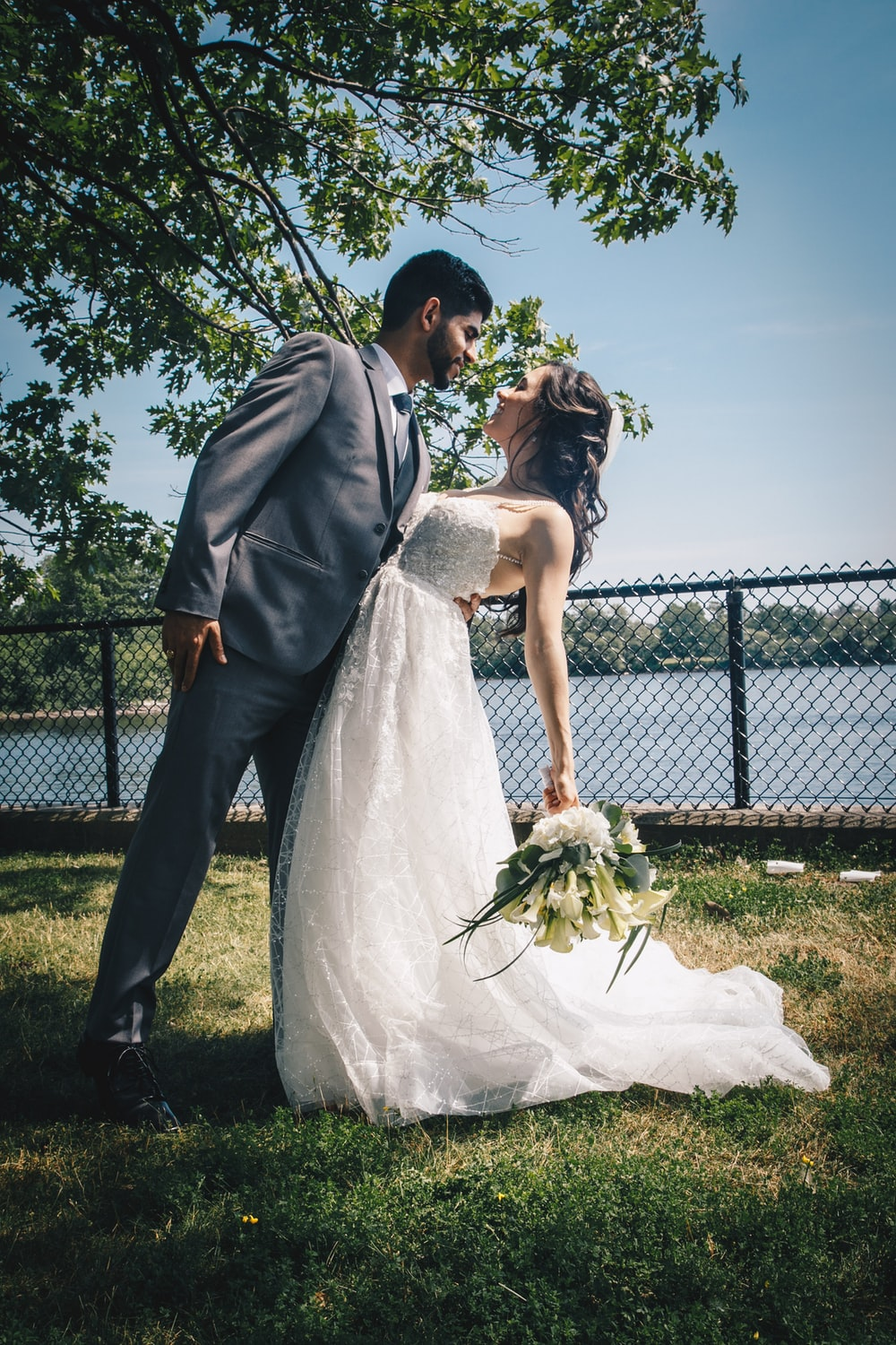 newly wed outside under green leaf tree near body of water during daytime