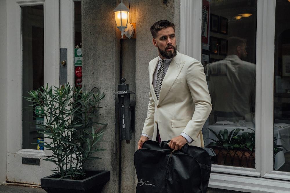 man carrying black garment bag