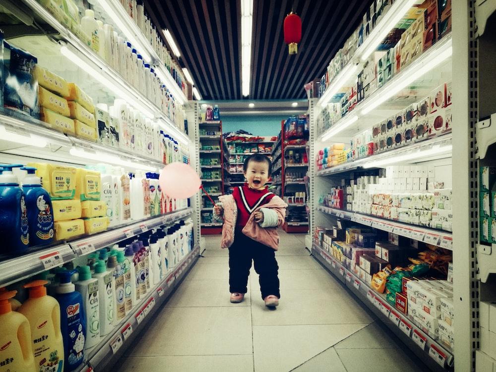 baby walking between white shelves