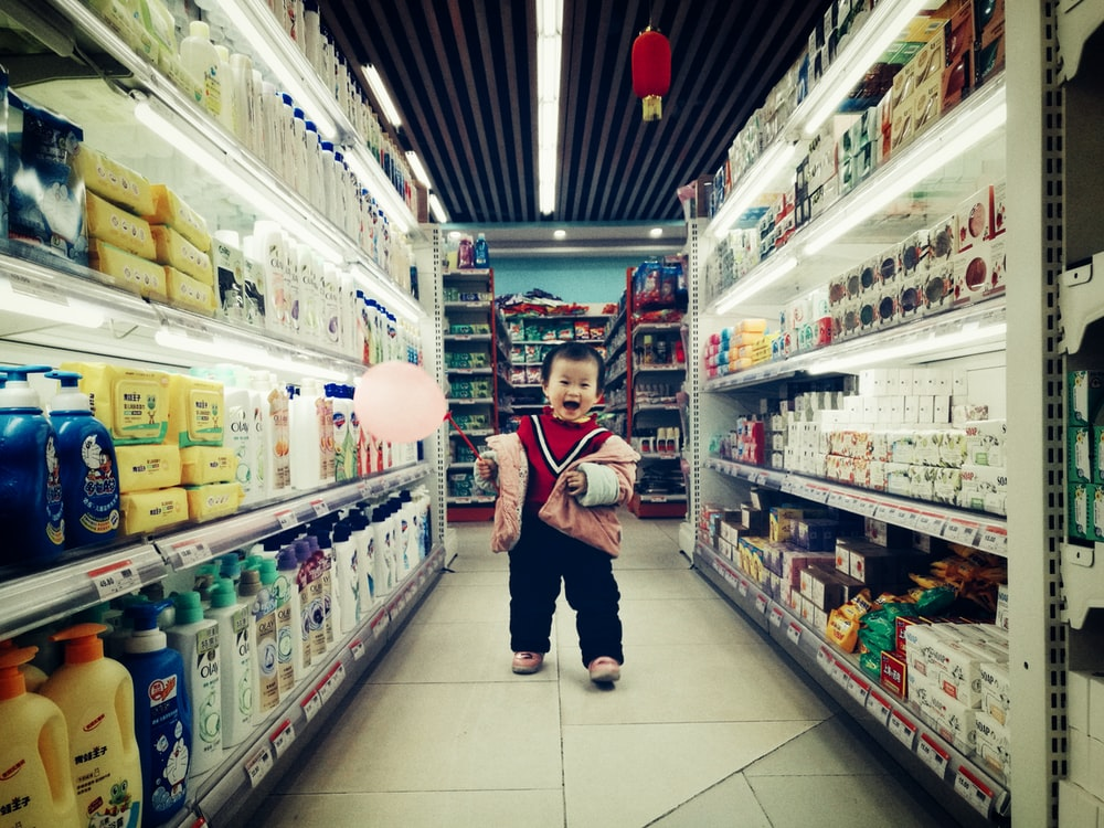 baby walking between white shelves