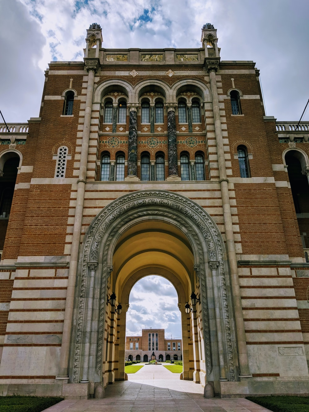 brown and white concrete arch building under dramatic clouds during daytime