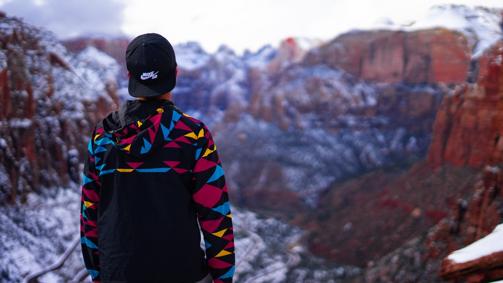 man wearing black, blue, and yellow hoodie and fitted cap facing snow covered mountain